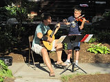 violin student performing fiddle tune with guitarist friend at block party