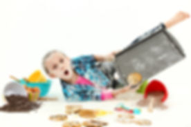 Adorable 7 year old girl baking cookies falling making mess over white background..jpg