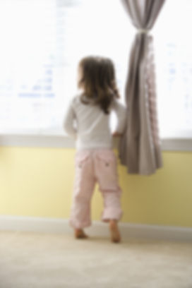 Caucasian girl toddler standing on tip toes looking out of window. (1).jpg
