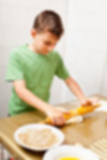 Portrait of a little boy in the kitchen using rolling pin to prepare the dough for cookies.jpg