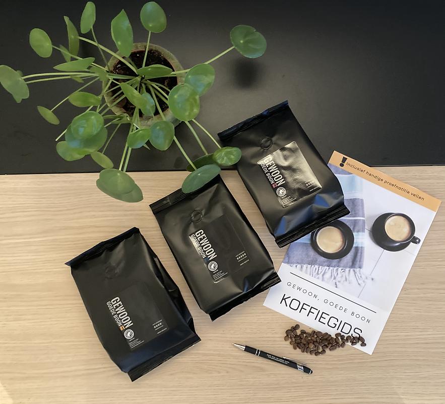 Drie smaken koffie met koffiegids en koffiebonen op bureau