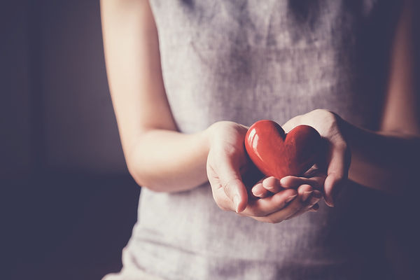 woman holding red heart, health insuranc