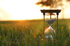 Hourglass in the grass time during sunse