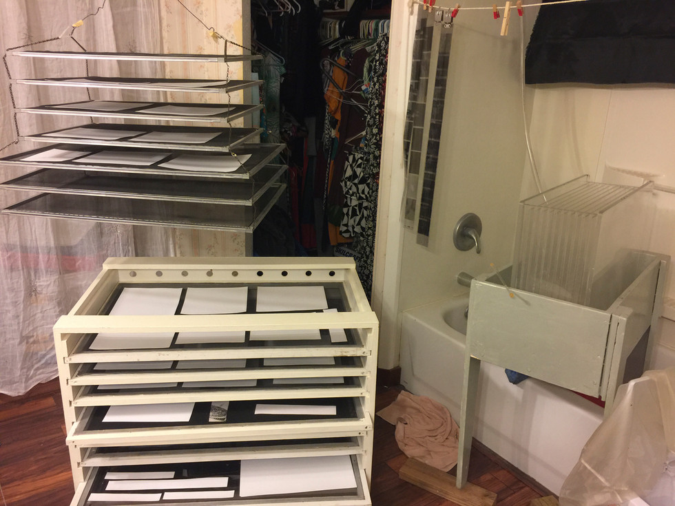 It ain't fancy, but it's super functional – my closet shares the darkroom space! I rigged up my archival washer to to the shower head, hung an extra dry rack from the ceiling, and can move my rolling drying rack around as needed.