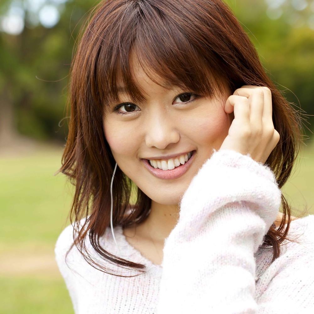 Jeune femme souriante, la main sur ses oreilles montrant son attention à écouter