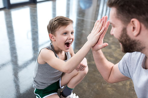 boy-giving-high-five-to-his-adult-friend
