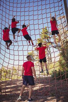 trainer-instructing-kids-in-net-climbing