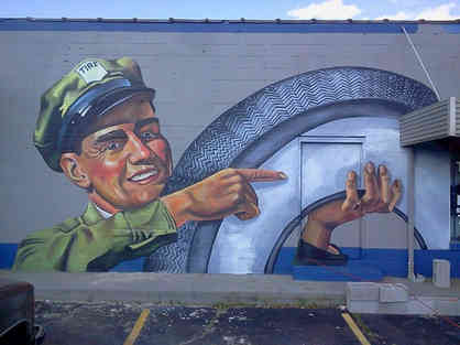 Hand painted mural of a tire attendant for Tire Mart of Barnesville, GA