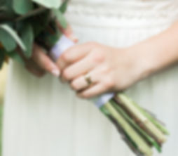 Brides Wedding ring on finger holding bouquet