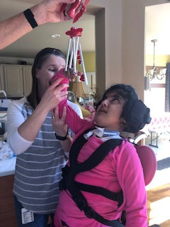 Teacher presents red wind chimes to student in her right upper visual field.  She provides support at her elbow and forearm.