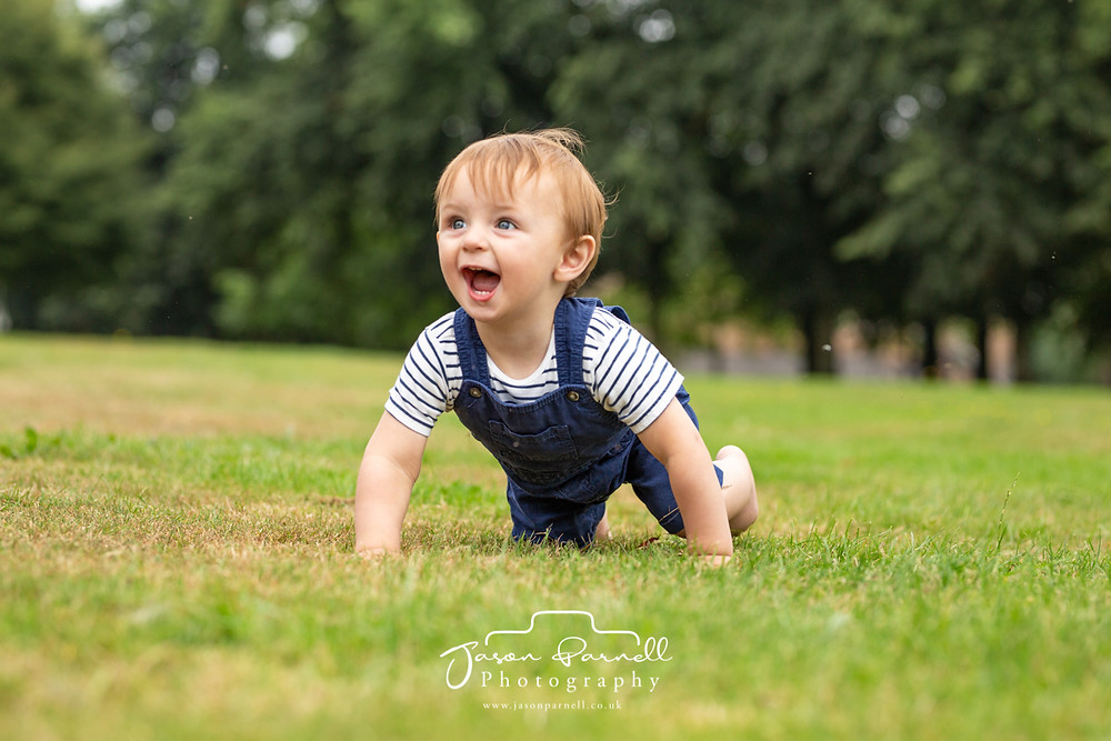 Child crawling on the grass in Carr Bank Park Mansfield