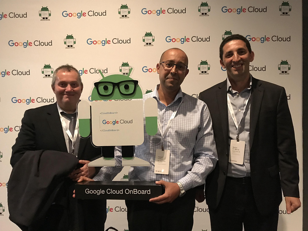 BI Expertise's CEO and founder, Youssef Loudiyi, holds the Google Cloud OnBoard mascot