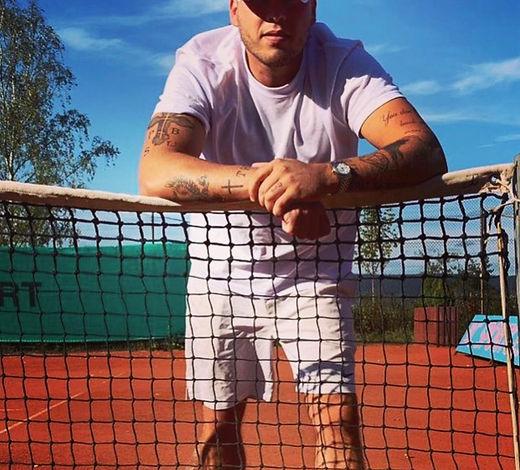 Der frühere Tennisspieler und heutige Tennistrainer Benedikt Müller steht auf einem Tennisplatz am Netz. Er ist bei der Tennisschule DS-Pro S.A. für das Tennistraining beim Tennisclub Bissen zuständig. Er kommt aus Kenn und hat dort die Tennisschule Tennis Müller-Cucka mit der Homepage mullercuckatennis.com