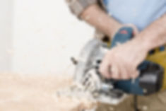 Picture of a man's hands holding and using an electric saw, with wood chips flying off the piece of wood at waist height.