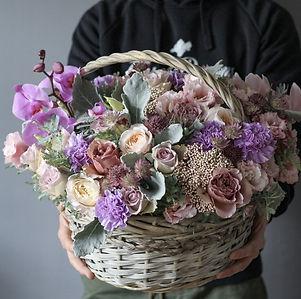 Корзинка с цветами в сиреневой гамме. В составке розы, диантусы, орхидеи и зелень сенецио. Корзина в подарок - купить в Москве