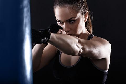 Studio shot of female boxer punching a b