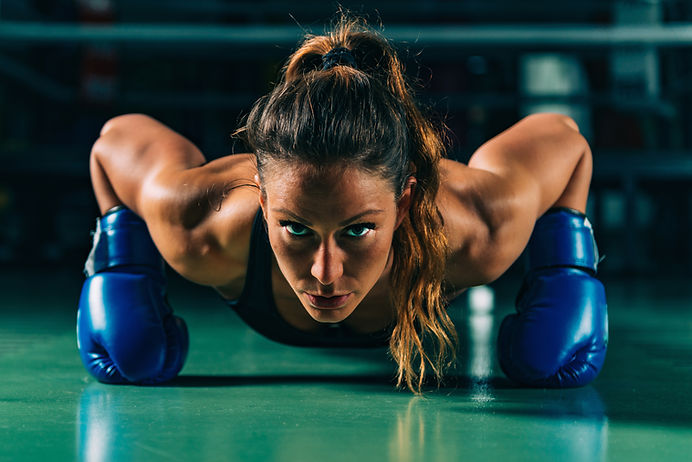 Woman on boxing training doing push ups.