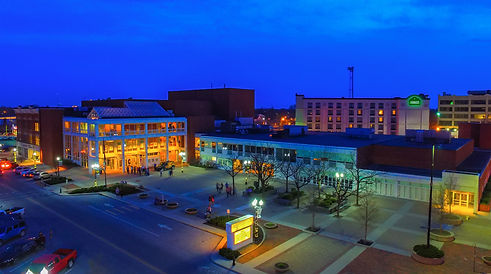 The Veterans Memorial Civic and Convention Center lit up at nighttime from an aerial view.