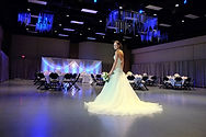 A bride standing in her white ballgown style wedding dress in the Lima Civic Center's ballroom, ideal for wedding receptions.