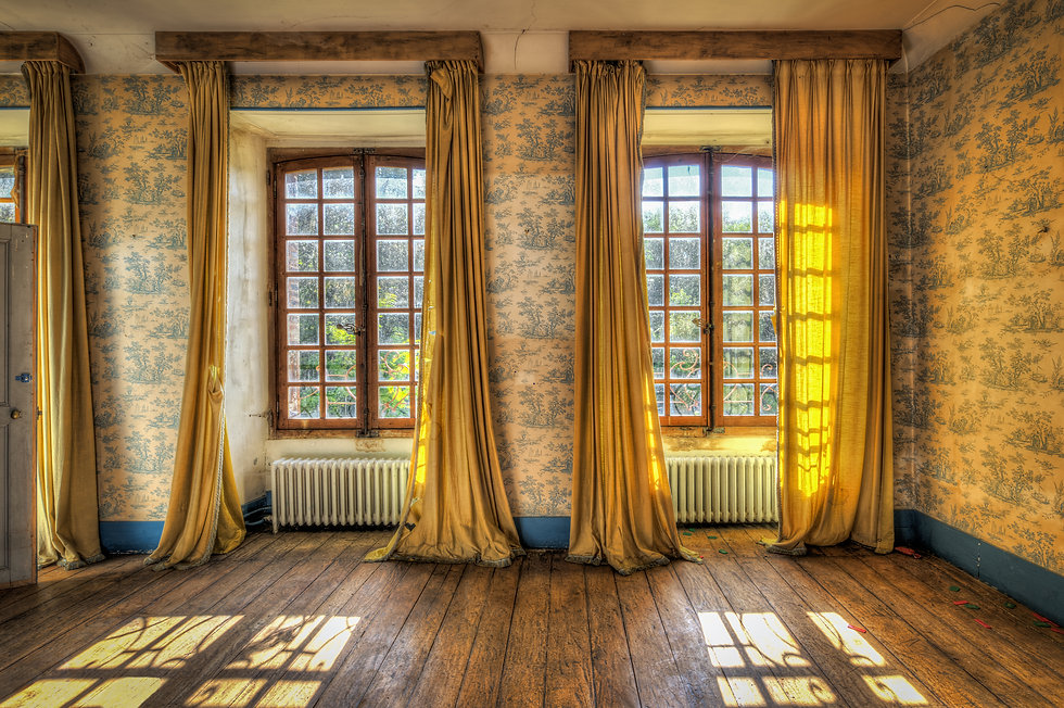 Windows with yellow curtains in an aband