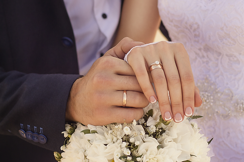 Closeup-shot-newlyweds-holding-hands-showing-wedding-rings for H and Z Diamond.png