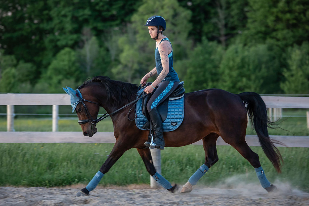 Woman with scoliosis and had spinal fusion surgery riding a horse.