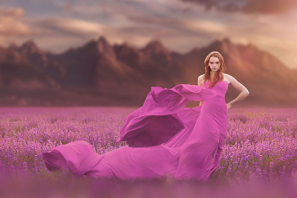 Model with scoliosis wearing a purple pink long flowing dress in a field of lavender.
