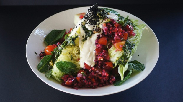 Iceberg, tomato and pomegranate wedge salad