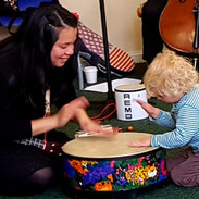 Mini musicians hitting the big drum