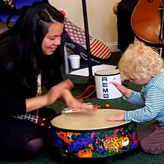Mini musicians hitting the big drum