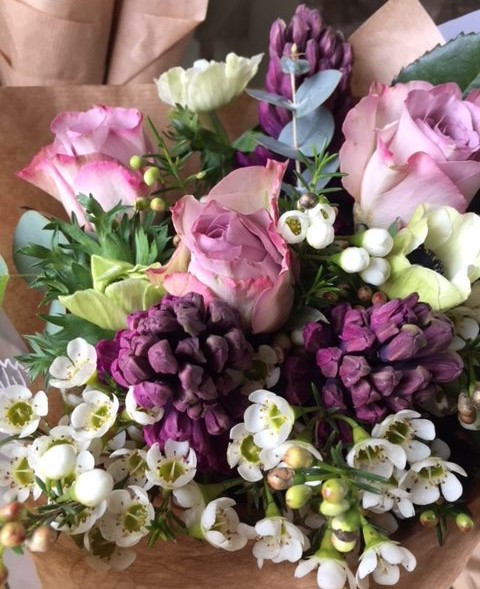 A bouquet of flowers with plum coloured hyacinths.