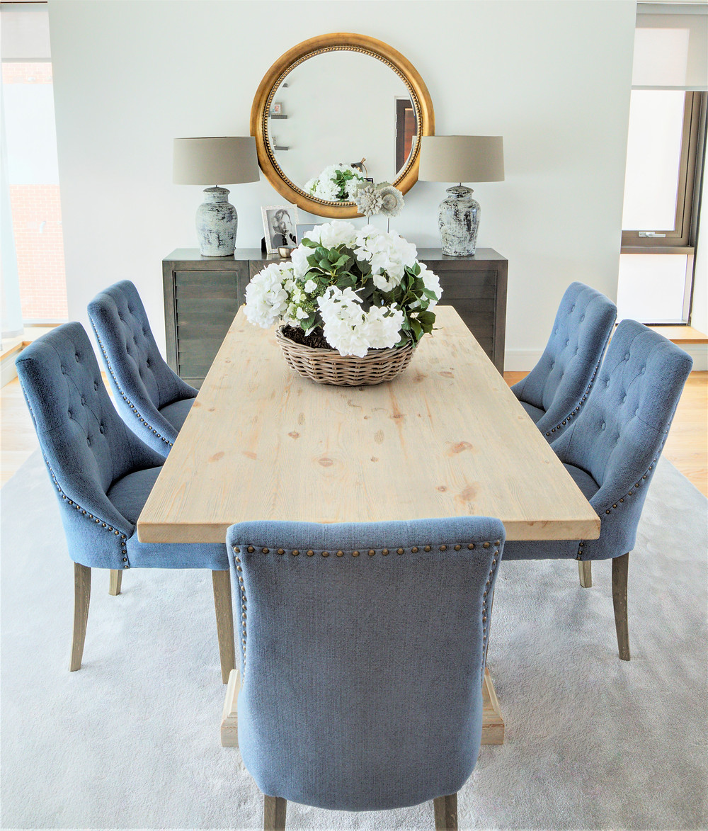 A dining table with blue dining chairs and hydrangeas. Interior design by Vesta Design