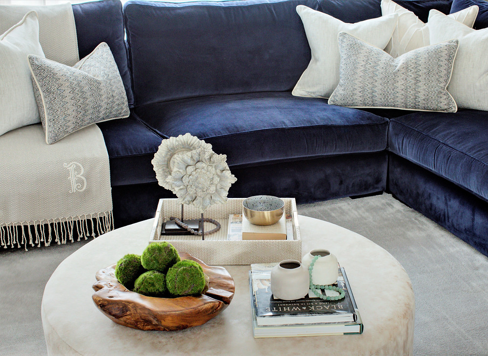 An ottoman coffee table with accessories, corner sofa and cushions. Interior design by Vesta Design