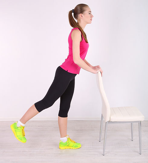 Young beautiful fitness girl exercising with chair in gym.jpg