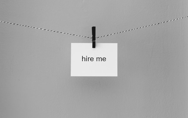 """A piece of card that says """"hire me"""" being held up by a peg"""