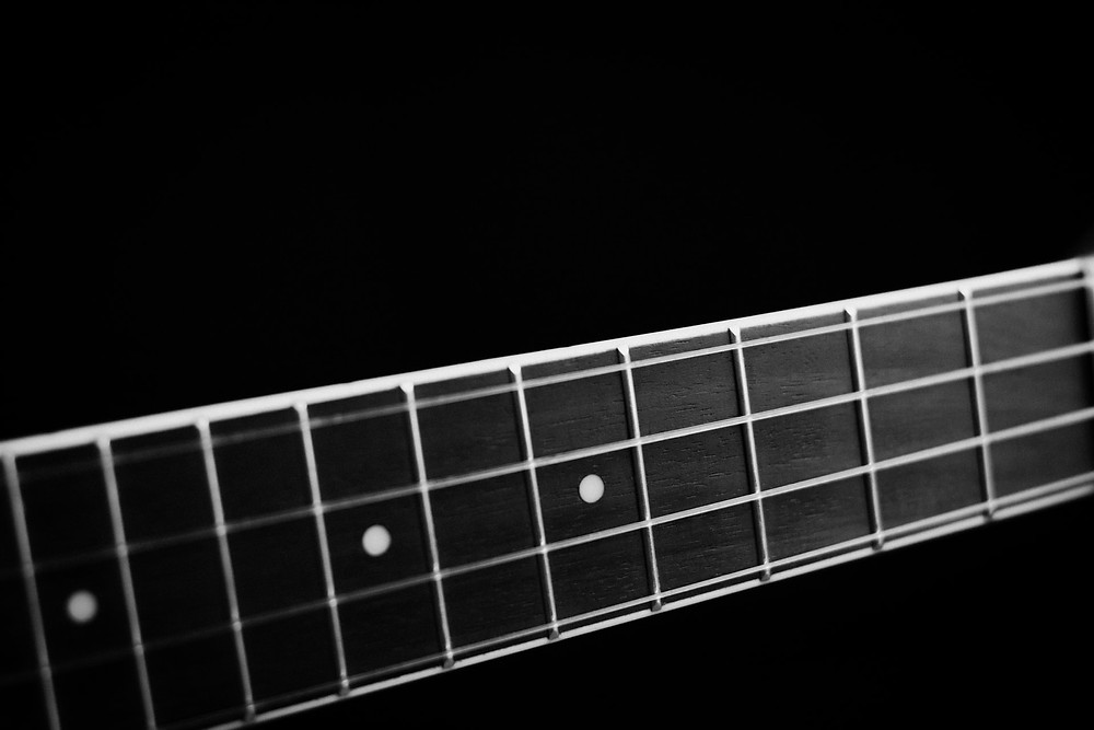 The neck of a bass guitar waiting to be played