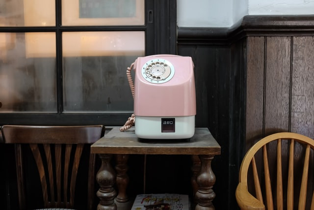 A strange looking pink telephone sits on an old table