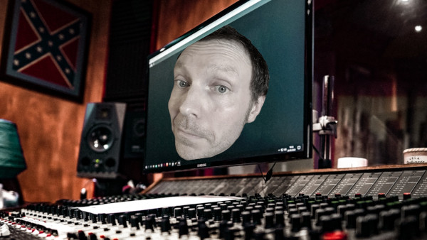 A mixing desk in a recording studio with Martin Whiskin's face on a computer monitor screen