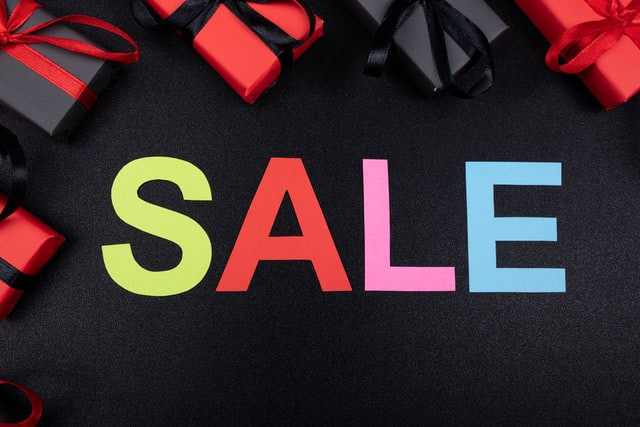 """The word """"SALE"""" in colourful letters, surrounded by gifts in black and red wrapping paper"""