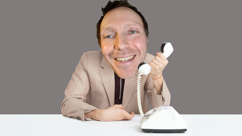 A happy looking man recording his business answerphone messages