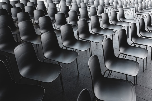 Many black plastic chairs waiting to be sat on