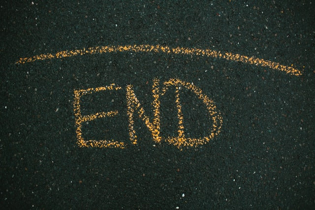 """The word """"end"""" written in yellow chalk on tarmac"""