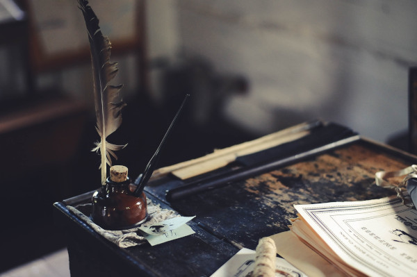 An ink well and quill sit on a stained old school desk