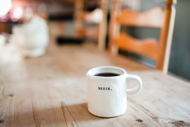 """A mug of coffee on a table. The mug has the word """"begin"""" written on it."""
