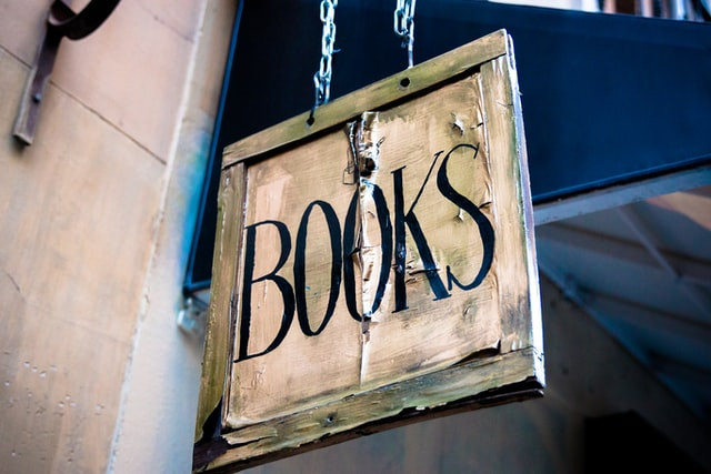 "A tatty sign hanging outside a shop that says ""BOOKS"""