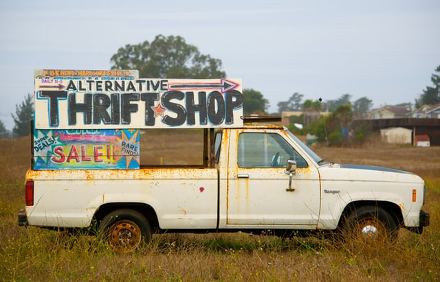 A rusty old truck with a sign for a thrift store in the back.