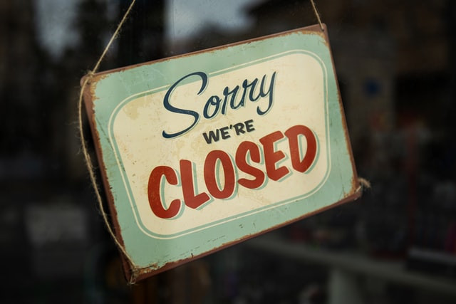 A closed sign hangs in a shop window