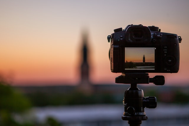 A camera taking a photo of a monument at dusk
