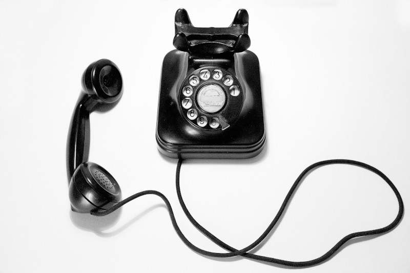 A disconnected rotary style telephone, black in colour