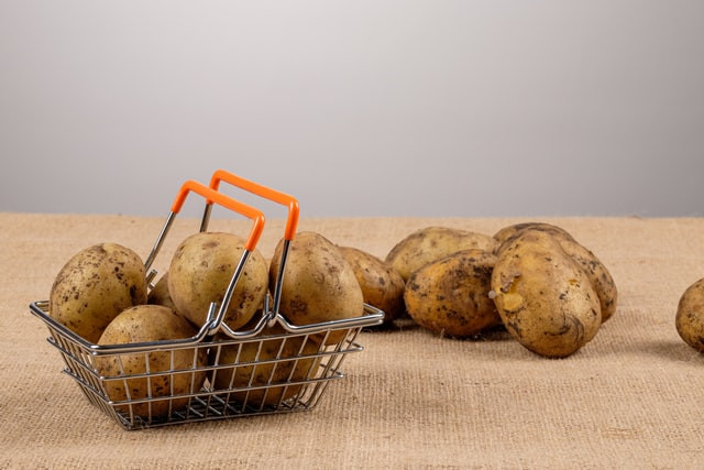 A tiny shopping basket with potatoes in it